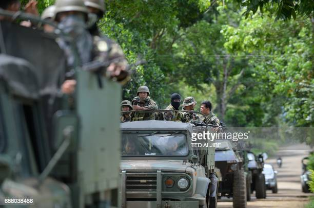 Philippine soldiers ride in miliary vehicles as they leave a military camp to reinforce troops fighting Muslim extremists in the city centre in...