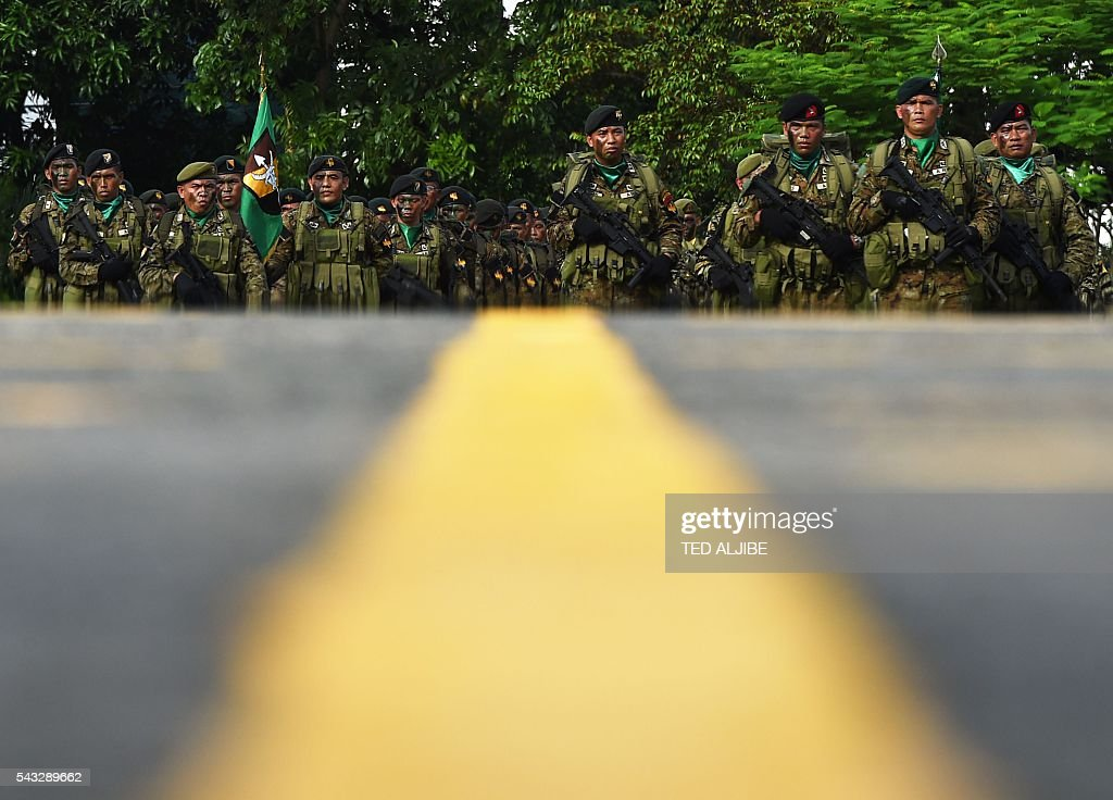 Philippine soldiers stand at attention during the testimonial parade for the outgoing president Benigno Aquino at the military headquarters in Manila on June 27, 2016. Aquino called on his countrymen on June 12 to fight attempts to take away their freedoms as he prepared to hand over power to president-elect Rodrigo Duterte, who has vowed to kill tens of thousands of criminals. / AFP / TED