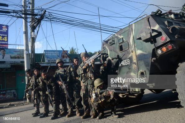 Philippine soldiers stand behind an armoured personnel carrier as they maneuver during an assault on Muslim rebel positions as the standoff enters...