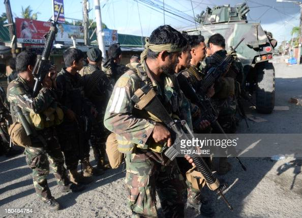 Philippine soldiers stand behind an armoured personnel carrier for cover during an assault on Muslim rebel positions as the standoff enters its fifth...