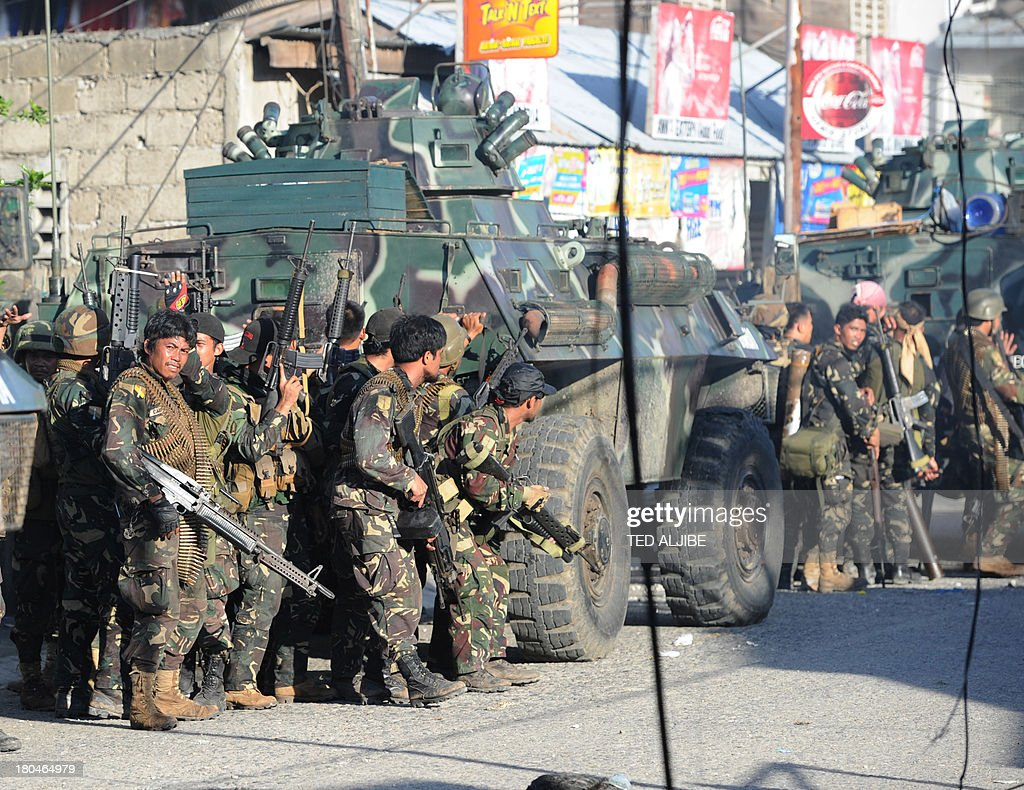 Philippine soldiers stand behind an armoured personnel carriers during an assault on Muslim rebel positions as the standoff enters its fifth day in...