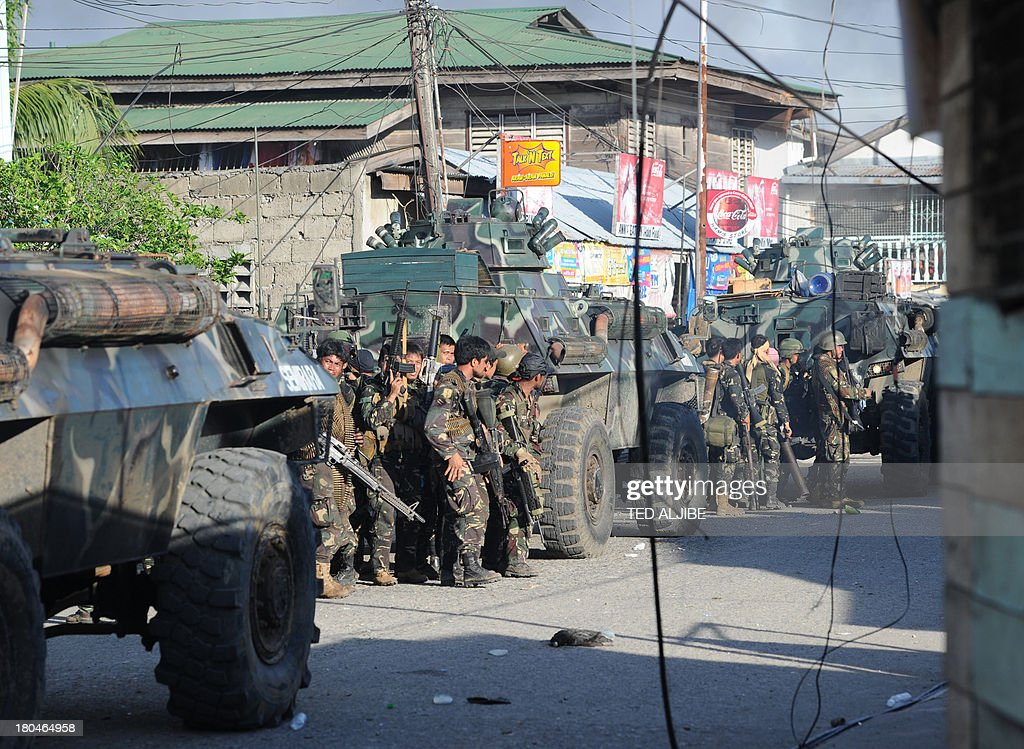 Philippine soldiers stand behind armoured personnel carriers during an assault on Muslim rebel positions as the standoff enters its fifth day in...