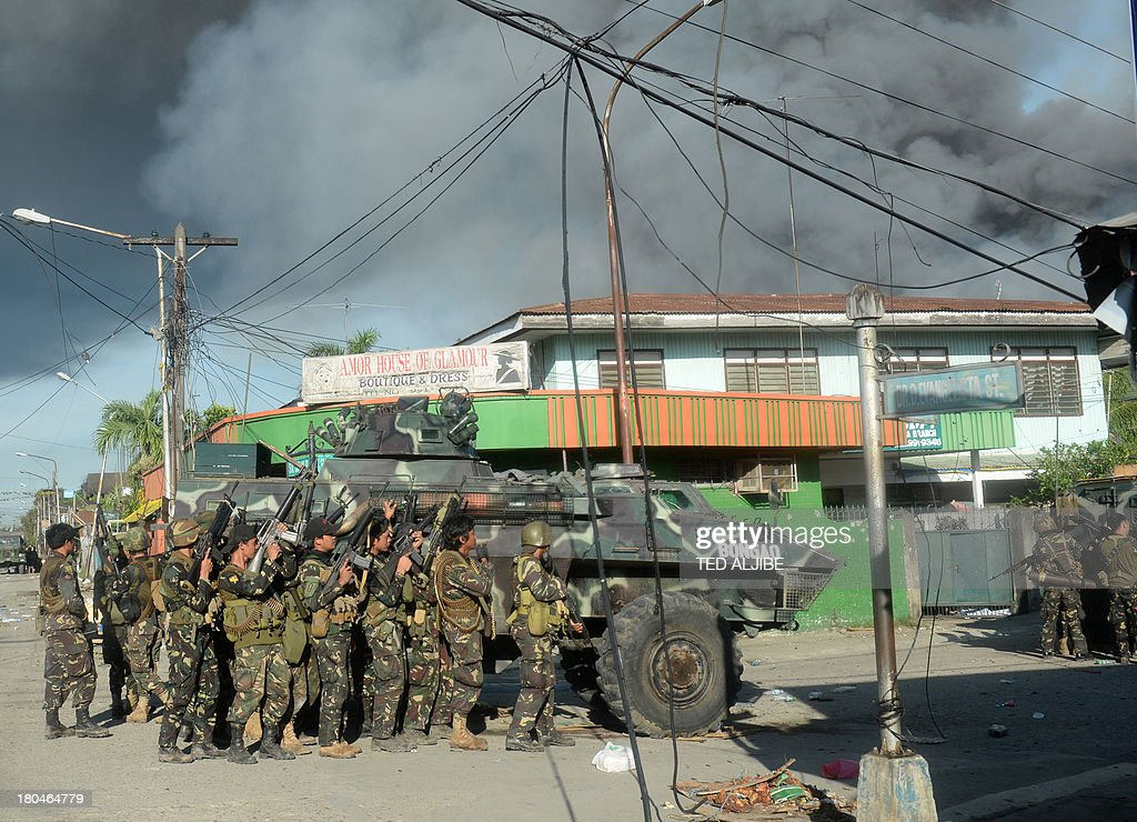 Philippine soldiers stand beside an armoured personnel carrier for cover during an assault on Muslim rebel positions while smoke billows from burning...