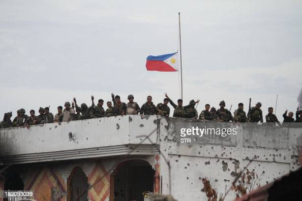 Philippine soldiers stand on the roof of a damaged house as a Philippine flag flutters at halfmast at Martha Street the scene of some of the heaviest...