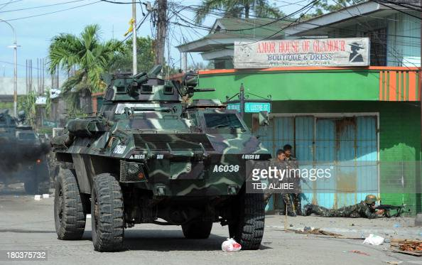 Philippine soldiers supported by an armored personnel carrier fire towards enemy position during a fire fight between government forces and Muslim...