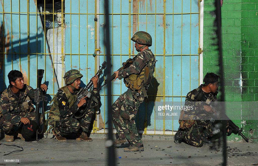 Philippine soldiers take cover behind a wall as a comrade (2nd R) maneuvers past during an assault on Muslim rebel positions as the stand-off enters its fifth day in Zamboanga City on September 13, 2013. Philippine President Benigno Aquino visited a southern city infiltrated by Muslim rebels September 13, vowing to end the crisis and warning the gunmen against harming civilian hostages or resorting to flagrant destruction. AFP PHOTO/TED ALJIBE