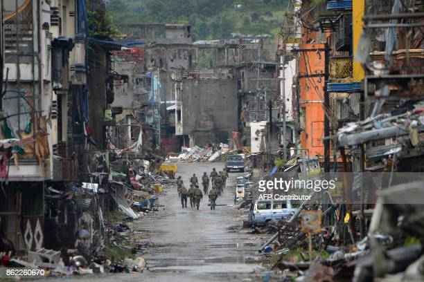TOPSHOT Philippine soldiers walk past destroyed buldings in Bangolo district after President Rodrigo Duterte declared Marawi City 'liberated' in...
