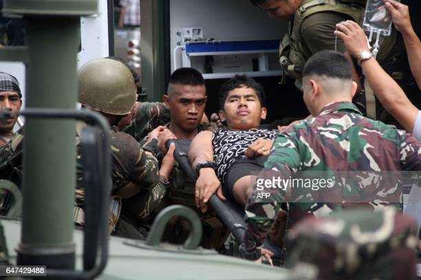 Philippine soldiers wounded in an ongoing clash with Islamist militants from the Abu Sayyaf group arrive at a military hospital in Jolo Sulu province...