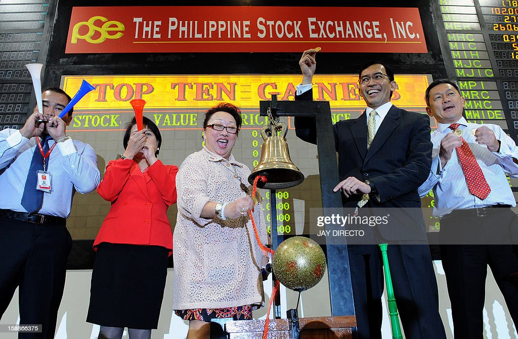 Philippine Stock Exchange (PSE) president and CEO, Hans Sicat (2nd R), gestures as PSE treasurer Ma. Vivian Yuchengco (3rd L) rings the bell to signal the start of the first day of trading in Manila on January 2, 2013. Philippine share prices closed 0.83 percent higher, up 48.26 points to close at 5,860.99, to a new all-time high on rising optimism that the US fiscal cliff would be averted, dealers said.