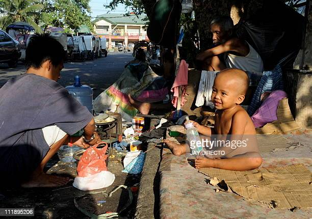 A Philippine street child holds her feeding bottle as her grandparents look on behind in Manila on April 8 2011 At night these children sleep in the...