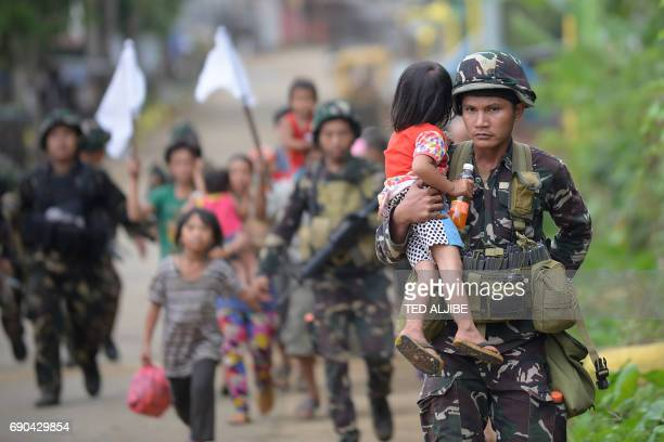 Philippine troops escort rescued civilians at a village on the outskirts of Marawi on the southern island of Mindanao on May 31 2017 Philippine...