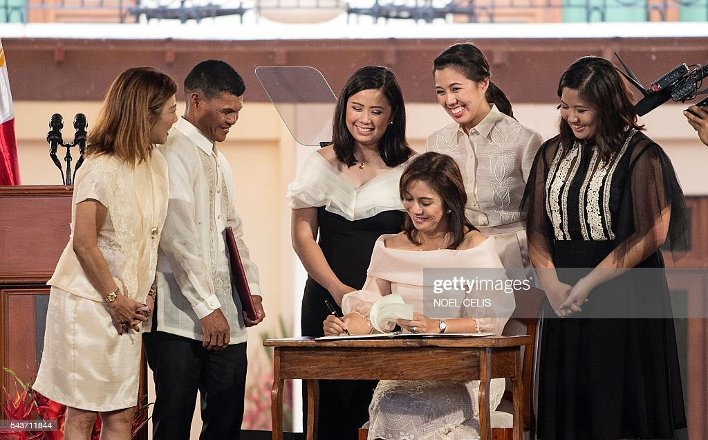 Philippine Vice President Leni Robredo signs papers during her Inauguration ceremonies with her daughters Jessica Marie (C), Jillian Therese (2nd R) and Janine Patricia (R) at the Quezon City Recepotion House in Manila on June 30, 2016. / AFP / NOEL