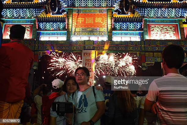 MANILA Philippines A couple takes a selfie as fireworks illuminate the sky above the Chinatown friendship arch the largest in the world located in...