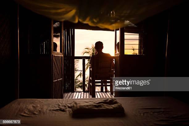 Philippines, Apo Island, man on the terrace of a wooden hut enjoying sunset