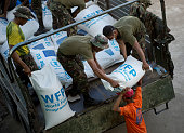 Philippines armed forces and volunteers unload sacks of rice in Dagami some 35kms inland south of Tacloban on November 18 2013 The United Nations...