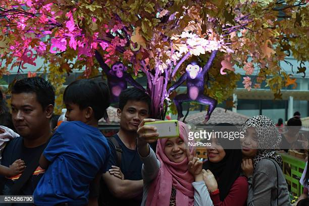 MANILA Philippines Filipino muslim women take a selfie in front of a 'prosperity tree' as part of a mall's attraction for the year of the Fire Monkey...