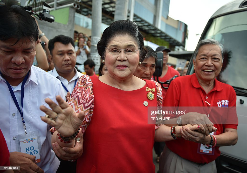 Philippines' former first lady Imelda Marcos (C) arrives for her son vice-presidential candidate Ferdinand Marcos Jnr's 'miting-de-avance' in Manila on May 5, 2016. / AFP / TED