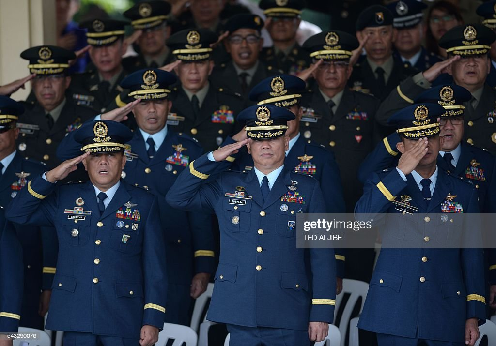 Philippines' military officials salute during the testimonial parade for outgoing president Benigno Aquino at the military headquarters in Manila on June 27, 2016. / AFP / TED