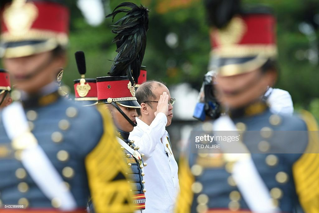 Philippines' outgoing president Benigno Aquino (C) salutes in frot of the colors during the testimonial parade for him at the military headquarters in Manila on June 27, 2016. Aquino called on his countrymen on June 12 to fight attempts to take away their freedoms as he prepared to hand over power to president-elect Rodrigo Duterte, who has vowed to kill tens of thousands of criminals. / AFP / TED