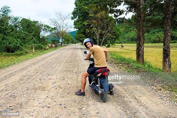 Philippines, Palawan island, man driving a motorcycle on a dirt road near El Nido