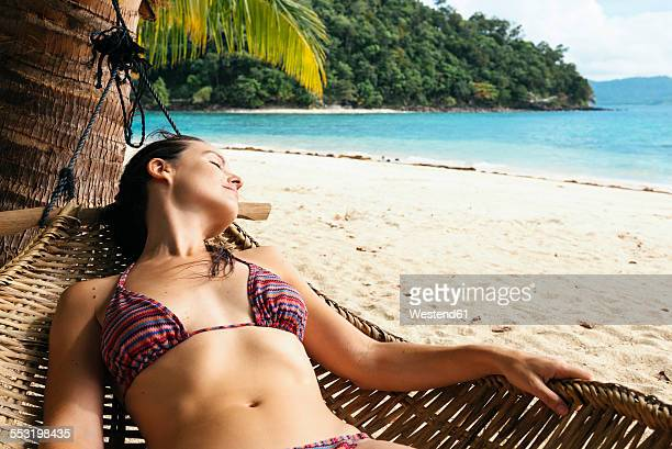 Philippines, Palawan, Woman relaxing on beach hammock