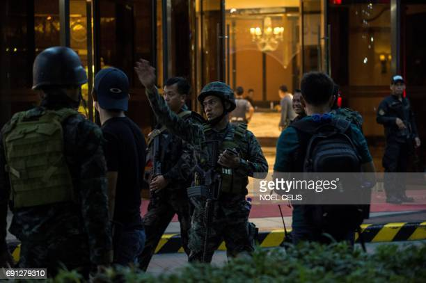 Philippines' police officers gesture as they stand guard by the Resorts World Hotel in Manila on June 2 2017 following an assault A gunman was on the...