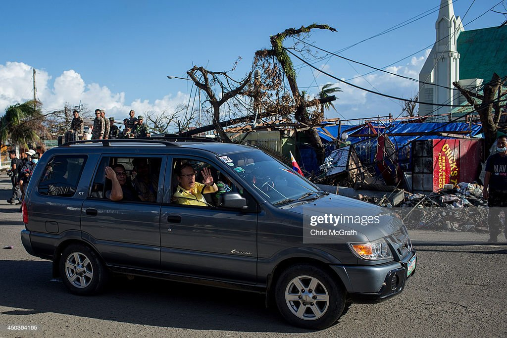Philippines President Benigno Aquino III waves to people on the street as he tours destroyed areas of Tacloban City following the recent super typhoon on November 18, 2013 in Leyte, Philippines. Typhoon Haiyan, which ripped through the Philippines on November 9, has been described as one of the most powerful typhoons ever to hit land, leaving thousands dead and hundreds of thousands homeless. Countries all over the world have pledged relief aid to help support those affected by the typhoon, however damage to the airport and roads have made moving the aid into the most affected areas very difficult. With dead bodies left out in the open air and very limited food, water and shelter, health concerns are growing.