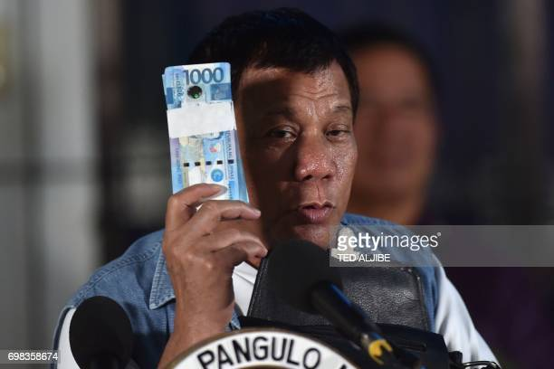 Philippines' President Rodrigo Duterte holds a wad of peso bills which he later gave to evacuees from Marawi while speaking to them in Iligan on the...