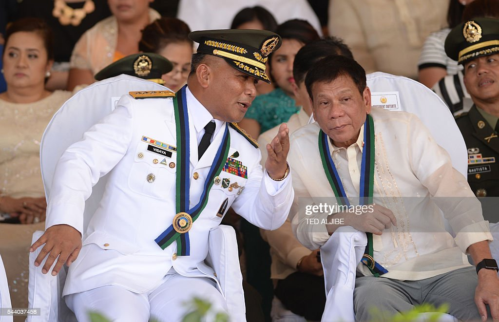 Philippines President Rodrigo Duterte (R) listens to newly-installed military chief Lieutenant General Ricardo during a military parade and change of command ceremony at the military headquarters in Manila on July 1, 2016. Duterte was sworn in as the Philippines' president June 30 -- and quickly launched a foul-mouthed vow to wipe out drug traffickers and even urged ordinary Filipinos to kill addicts. / AFP / TED