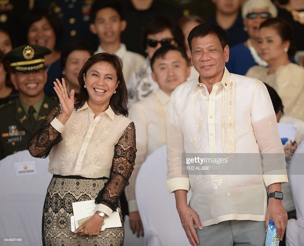 Philippines President Rodrigo Duterte (R) poses for photographs with vice-president Leni Robredo after the military parade at the military headquarters in Manila on July 1, 2016. Duterte was sworn in as the Philippines' president June 30 -- and quickly launched a foul-mouthed vow to wipe out drug traffickers and even urged ordinary Filipinos to kill addicts. / AFP / TED