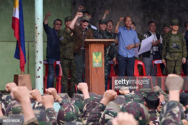 Philippines President Rodrigo Duterte raises a clenched fist along with soldiers as he shouts declaring Marawi 'liberated' during a ceremony inside...