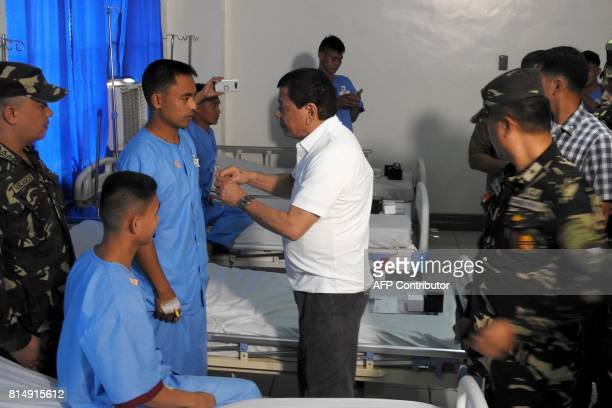 Philippine's president Rodrigo Duterte salutes at one of the 12 wounded soldiers at the Camp Teodulfo Bautista hospital in Jolo Sulu on the southern...