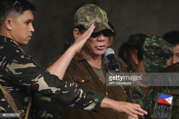 TOPSHOT Philippines' President Rodrigo Duterte salutes in front of soldiers after declaring Marawi City 'liberated' during a ceremony inside the...