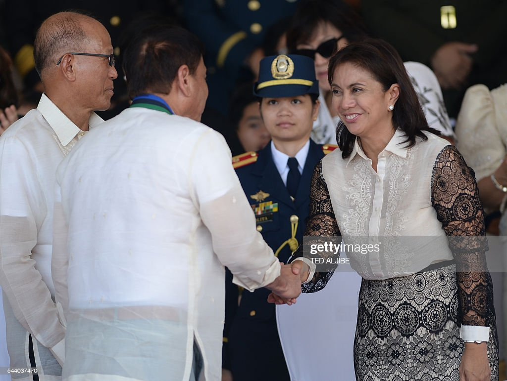 Philippines President Rodrigo Duterte (R) shake hands with vice-president Leni Robredo after the military parade at the military headquarters in Manila on July 1, 2016. Duterte was sworn in as the Philippines' president June 30 -- and quickly launched a foul-mouthed vow to wipe out drug traffickers and even urged ordinary Filipinos to kill addicts. / AFP / TED