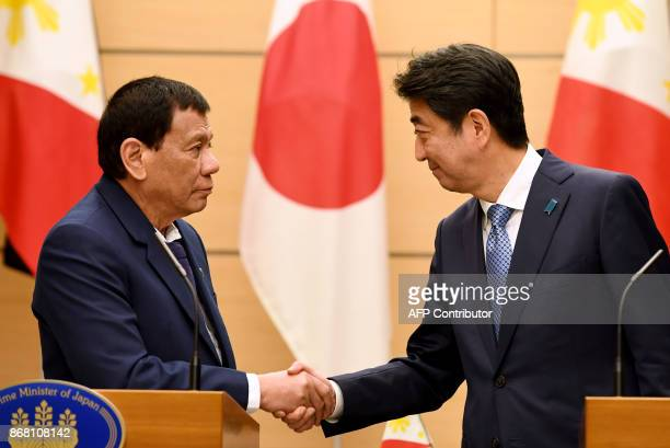 Philippines President Rodrigo Duterte shakes hands with Japanese Prime Minister Shinzo Abe at the end of their signing ceremony and joint remarks...