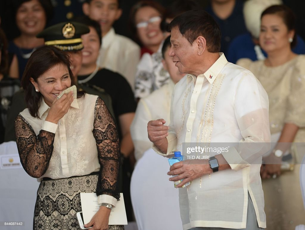 Philippines President Rodrigo Duterte (R) talks to vice-president Leni Robredo after the military parade at the military headquarters in Manila on July 1, 2016. Duterte was sworn in as the Philippines' president June 30 -- and quickly launched a foul-mouthed vow to wipe out drug traffickers and even urged ordinary Filipinos to kill addicts. / AFP / TED