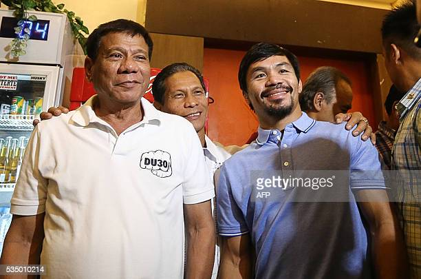 Philippines' Presidentelect Rodrigo Duterte stands beside boxing icon and newly elected Senator Manny Pacquiao at a meeting in Davao in southern...