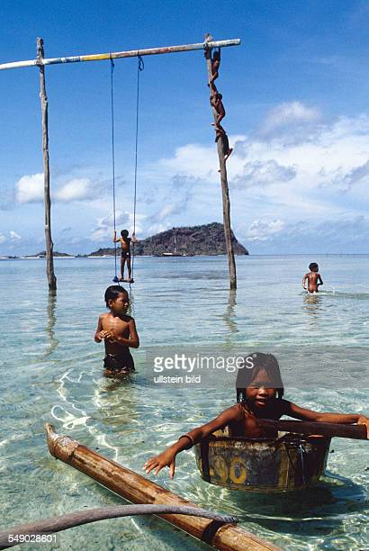 Badjao children climbing up a pole stuck in the water of the island Marunga