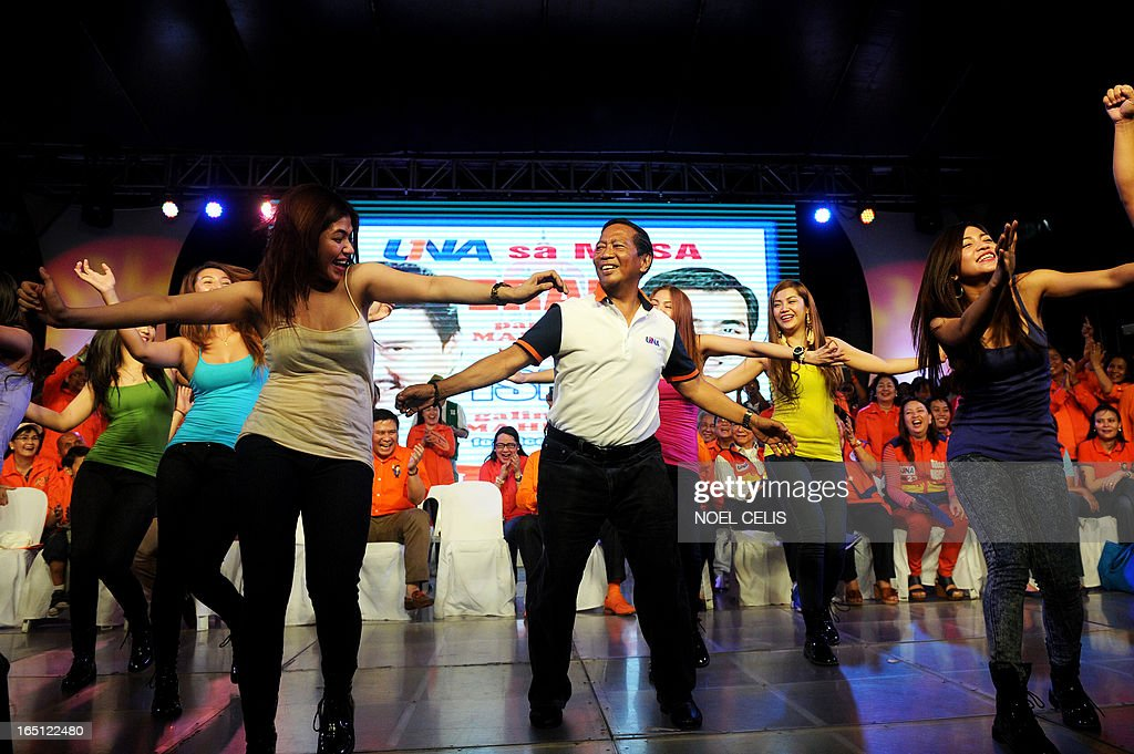 Philippine's Vice President Jejomar Binay (C) dances with performers during Former Philippine president and candidate for mayor of Manila Joseph Estrada's campaign launch on March 31, 2013 in Manila. In typically colourful fashion, graft-tainted former Philippine president Joseph Estrada launched his campaign for mayor of Manila Sunday in what he described as his 'last hurrah' in politics. The one-time movie actor, who turns 76 on April 19, said he wanted to end his political career as the mayor of a city where he was born and in whose sprawling slums he remains hugely popular. AFP PHOTO / NOEL CELIS