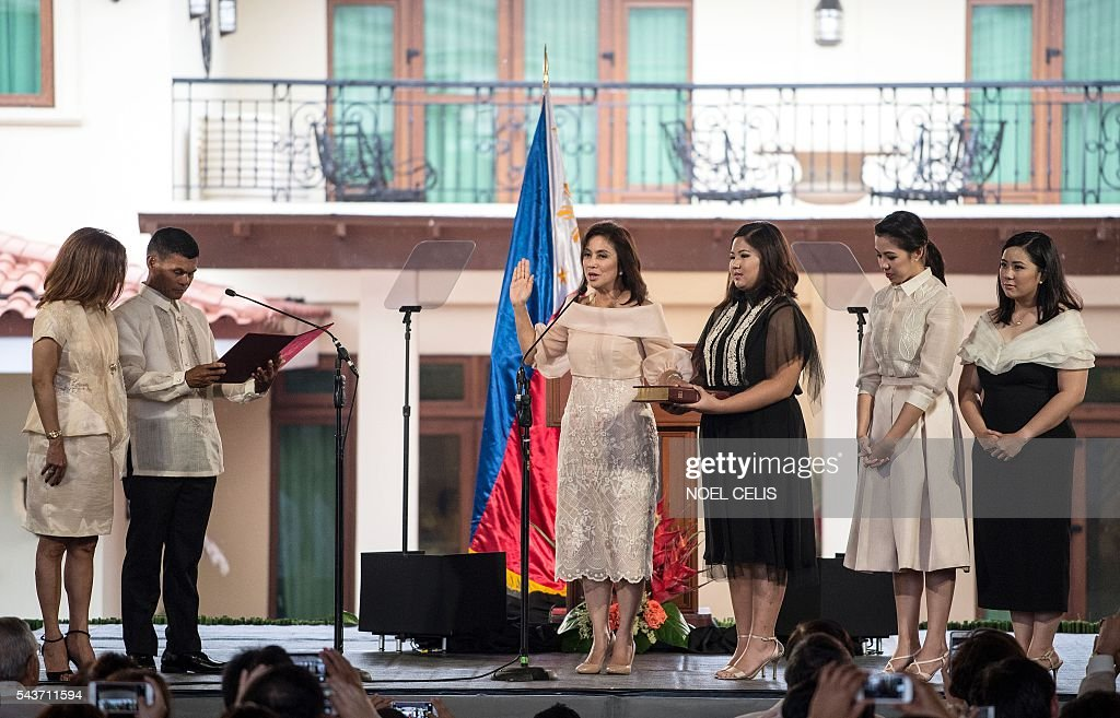 Philippines Vice President Leni Robredo (L) takes an oath administered by Barangay Captain Ronaldo Coner (2nd L) during her inauguration ceremonies with her daughters Jillian Therese (2nd L), Janine Patricia (2nd R) and Jessica Marie (R)at the Quezon City Recepotion House in Manila on June 30, 2016. / AFP / NOEL