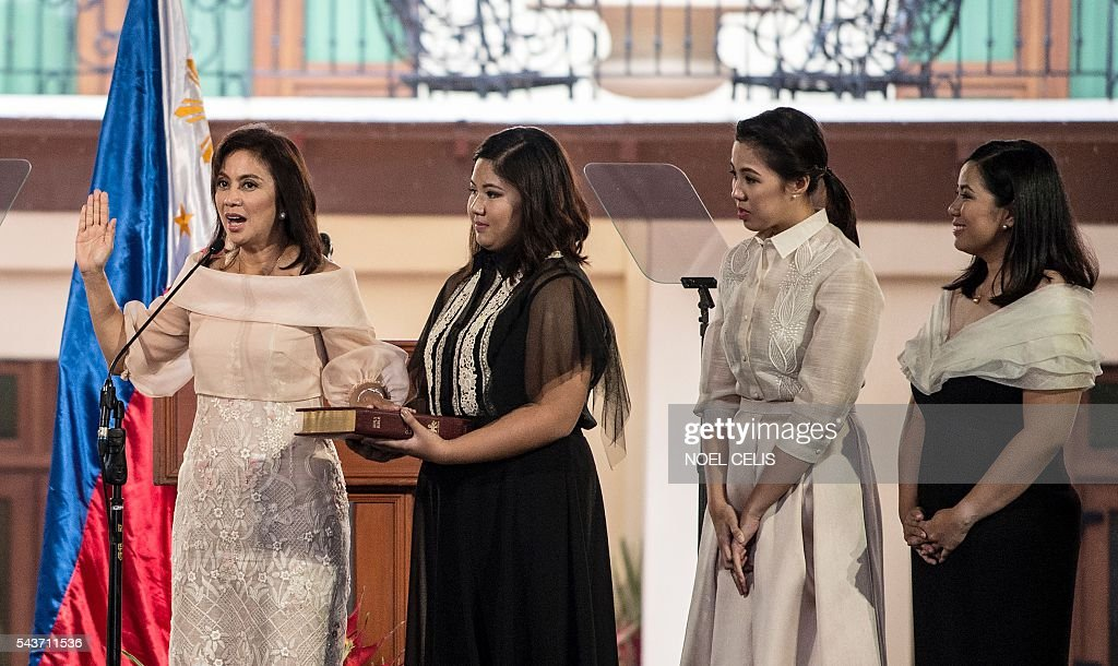 Philippines Vice President Leni Robredo (L) takes an oath during her inauguration ceremonies with her daughters Jillian Therese (2nd L), Janine Patricia (2nd R) and Jessica Marie (R)at the Quezon City Recepotion House in Manila on June 30, 2016. / AFP / NOEL