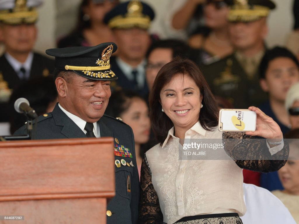 Philippines vice-president Leni Robredo (R) takes a selfie with a military officer during a military parade in honour of President Rodrigo Duterte (not pictured) at the military headquarters in Manila on July 1, 2016. Duterte was sworn in as the Philippines' president June 30 -- and quickly launched a foul-mouthed vow to wipe out drug traffickers and even urged ordinary Filipinos to kill addicts. / AFP / TED
