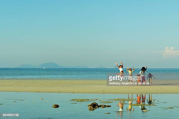 Philippines, Western Visayas, Iloilo, Sicogon, children playing and jumping on the beach at low tide