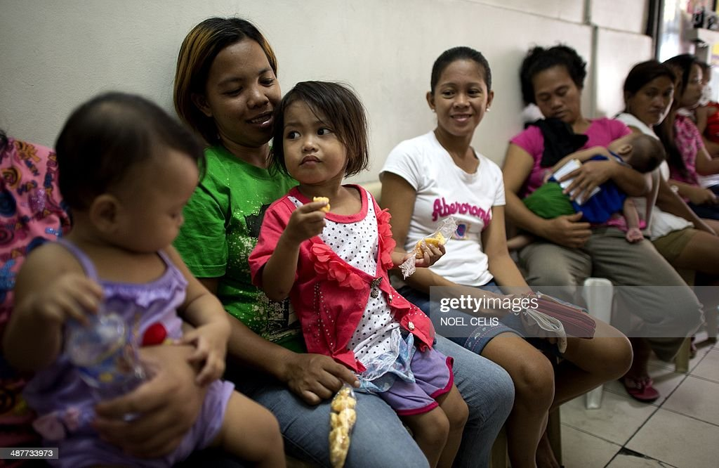 STORY 'Philippines-church-divorce-population,FOCUS' by Jason GUTIERREZ Filipina mothers line up to receive contraceptives at a health clinic in Manila on April 23, 2014. The Philippines has long been known as the Catholic Church's Asian stronghold, but a new birth control law highlights an increasingly liberal shift that could next see divorce legalised, activists and religious leaders say.