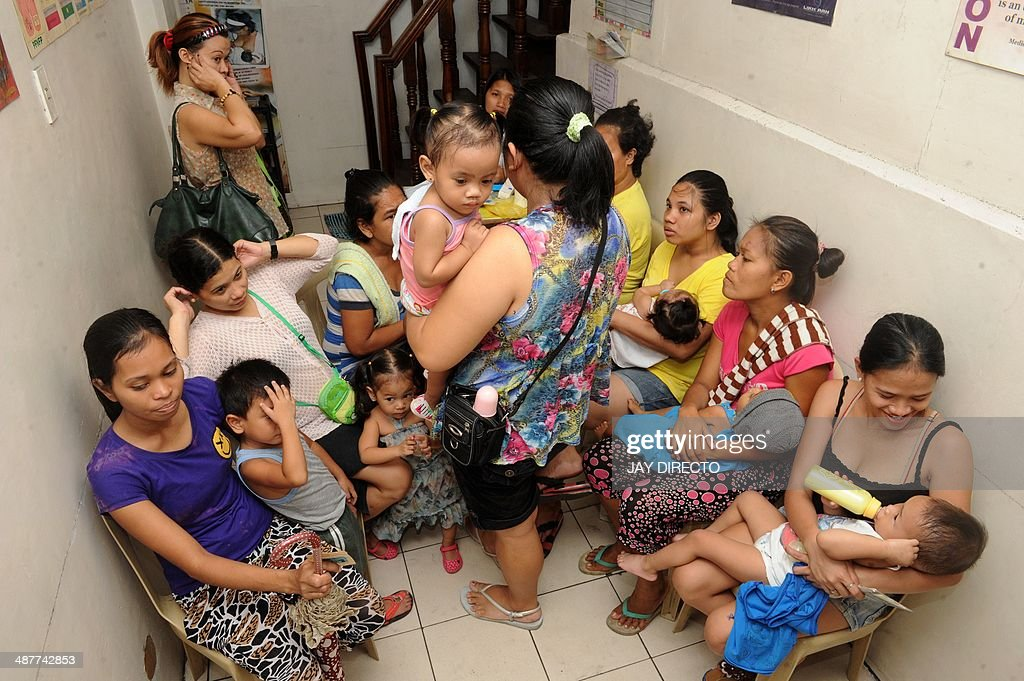 Philippines-church-divorce-population,FOCUS by Jason GUTIERREZ Mothers with children queue at likhaan center for women's health to consult for free family planing method in Manila on May 2, 2014. The Philippines has long been known as the Catholic Church's Asian stronghold, but a new birth control law highlights an increasingly liberal shift that could next see divorce legalised, activists and religious leaders say. AFP PHOTO / Jay DIRECTO