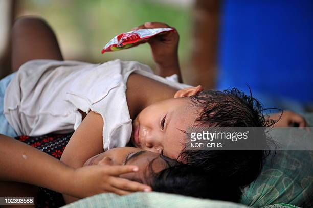 STORY 'PhilippinesFloodPoverty' by Cecile Morella In this photo taken on June 11 a girl comfors her baby brother on their shanty house made of...