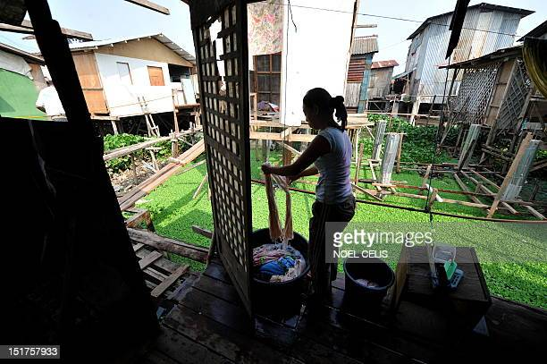 STORY 'PhilippinesFloodPoverty' by Cecile Morella O this photo taken on June 11 a woman washes some clothes on her shanty house made of plywood and...