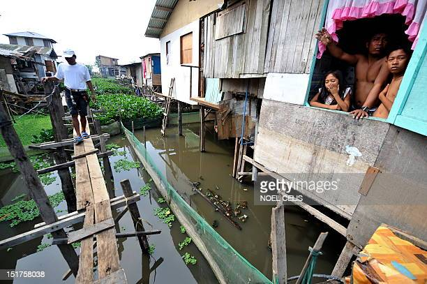 STORY 'PhilippinesFloodPoverty' by Cecile Morella o this photo taken on June 11 a man walks on flimsy wooden footbridges to cross to his shanty house...