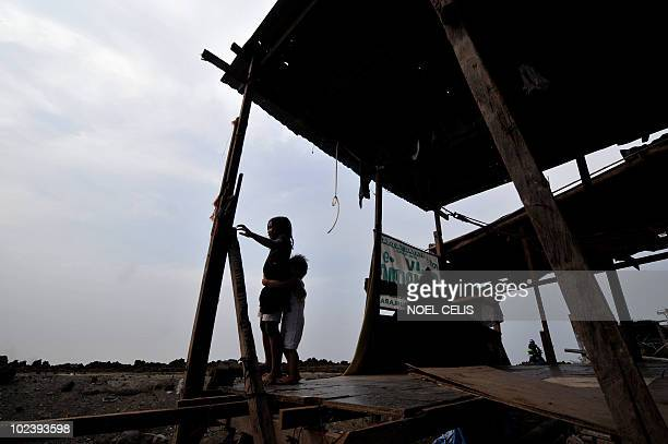 STORY 'PhilippinesFloodPoverty' by Cecile Morella On this photo taken on June 11 children look out on their shanty house made of plywood on the shore...