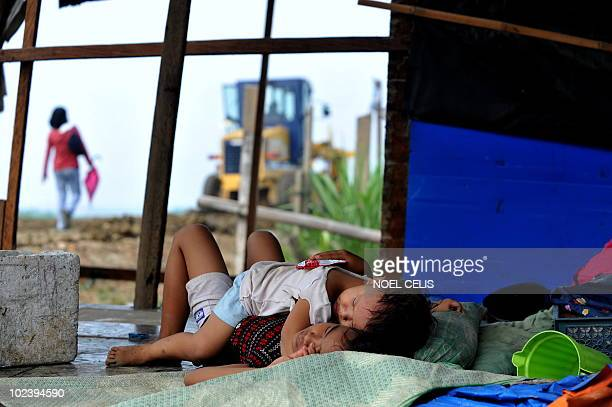 STORY 'PhilippinesFloodPoverty' by Cecile Morella on this photo taken on June 11 a girl comforts her baby brother in their shanty house made of...